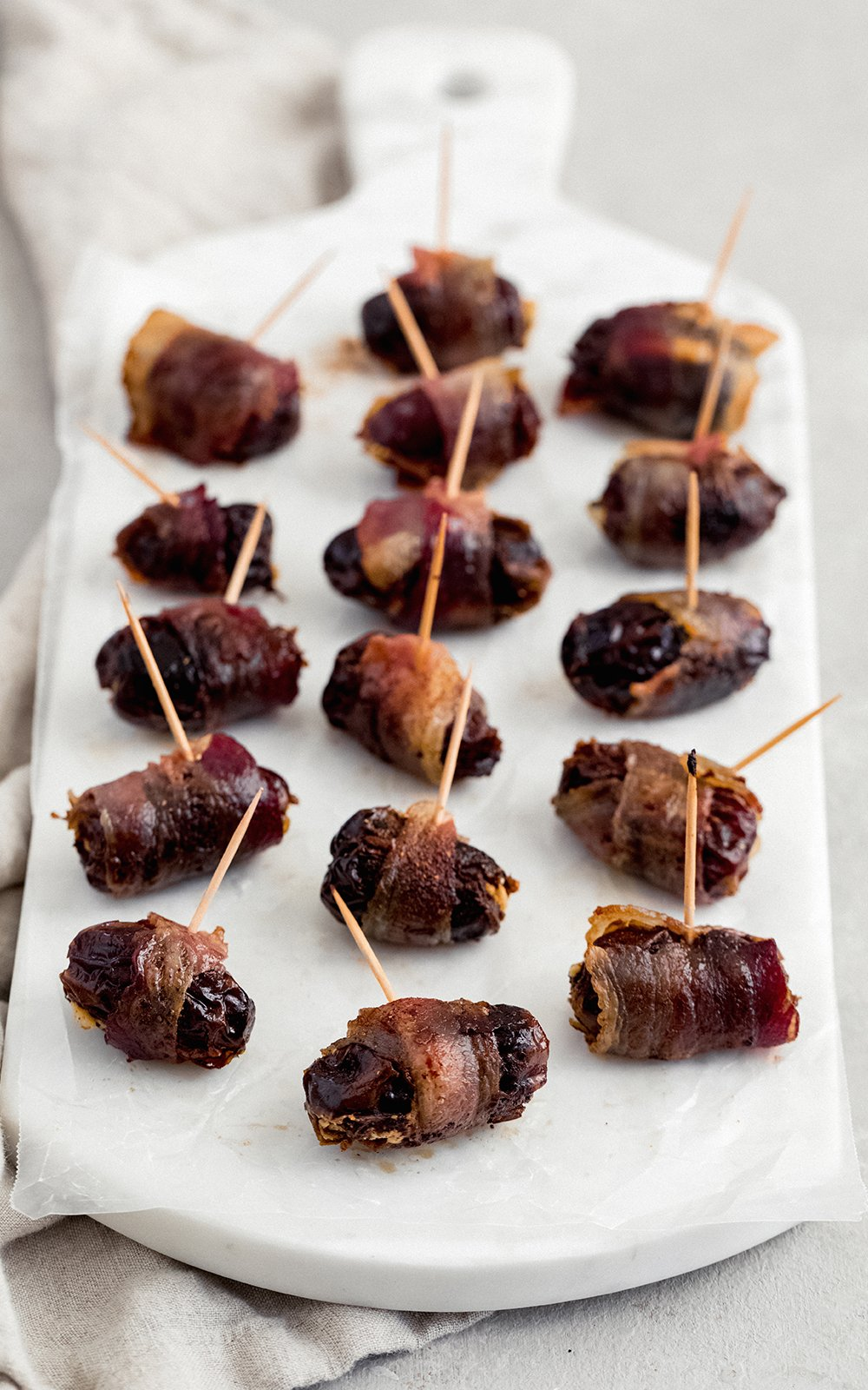 bacon wrapped goat cheese stuffed dates with toothpicks on a marble serving tray