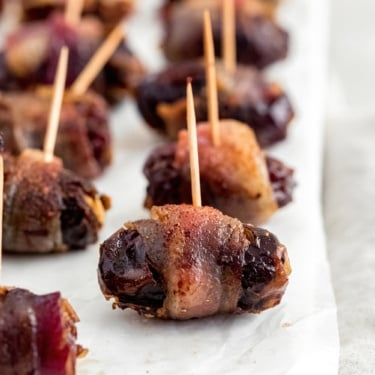 bacon wrapped dark chocolate and goat cheese stuffed dates on wax paper