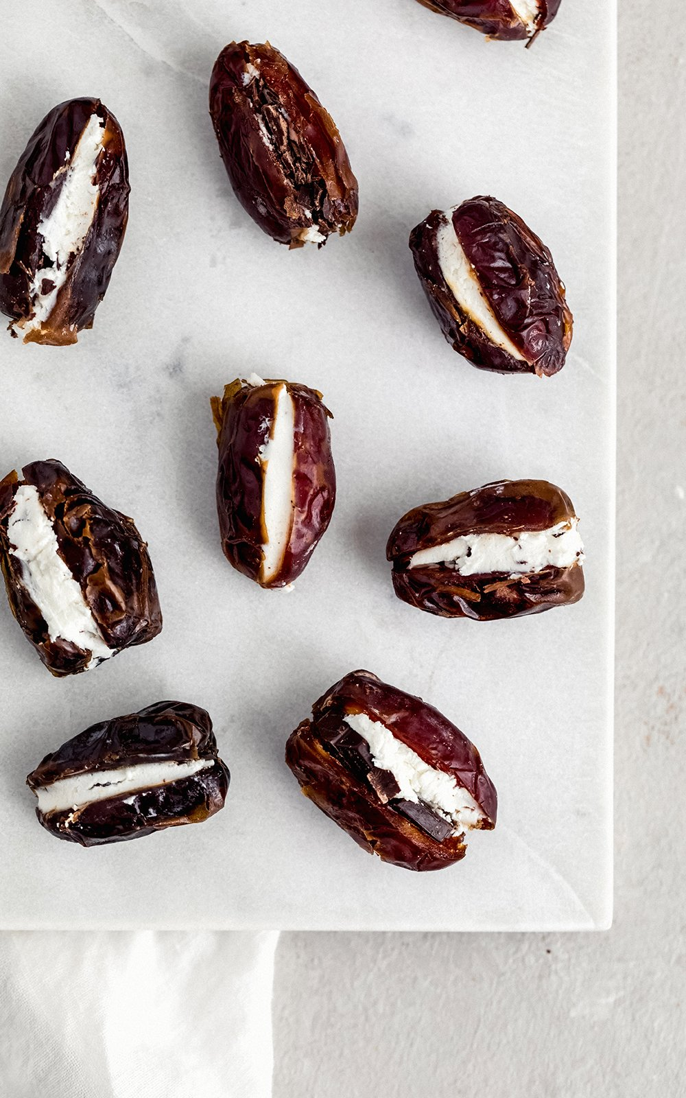 goat cheese stuffed dates on a marble board