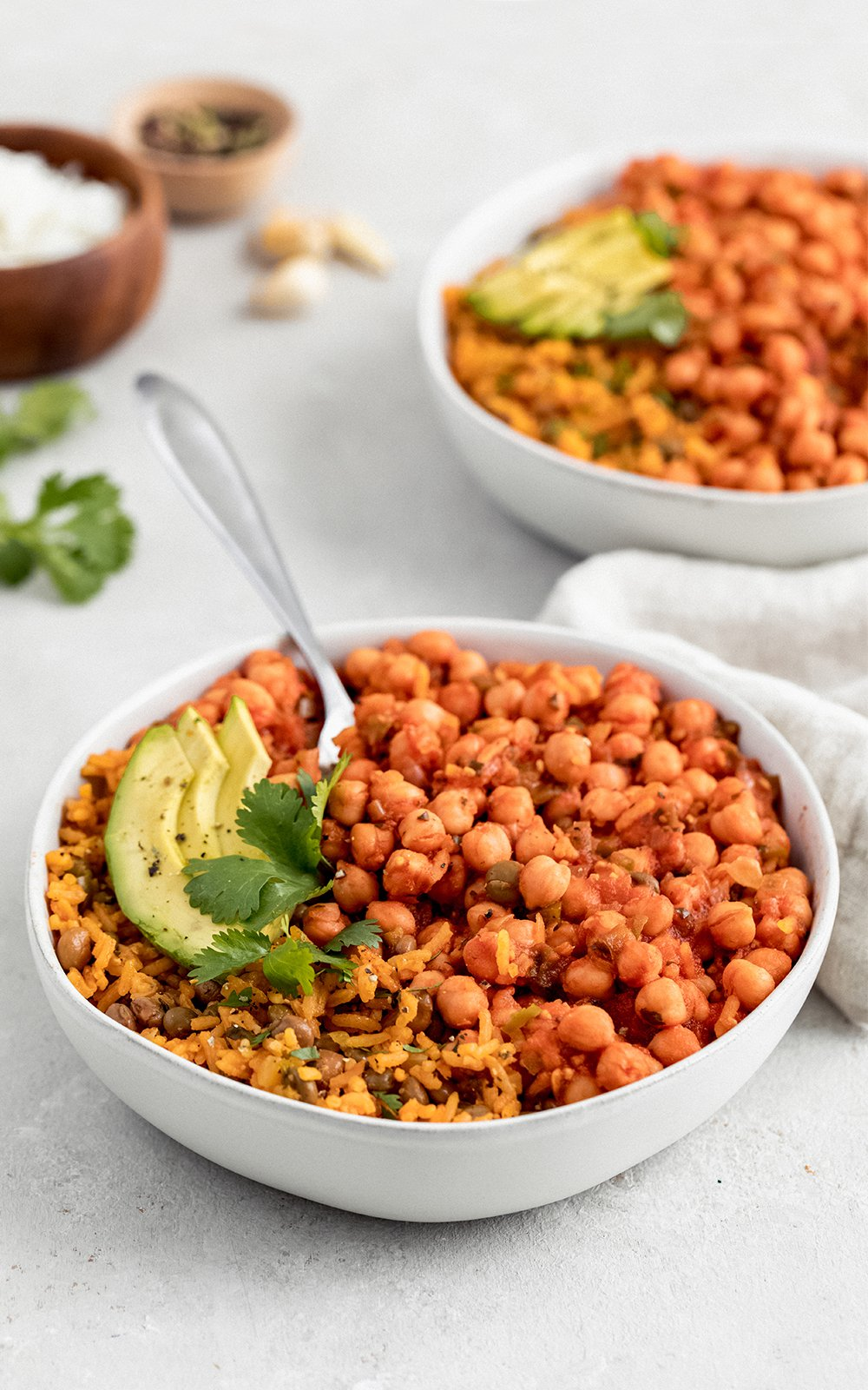 chickpeas in sofrito in a bowl topped with avocado