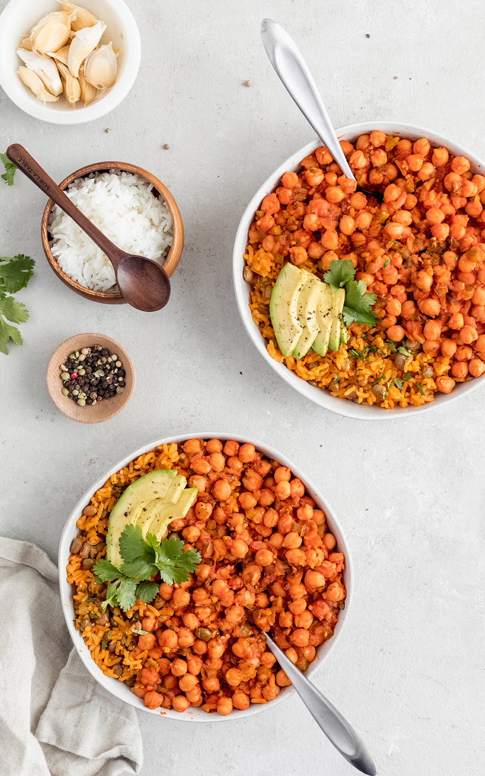 chickpeas in sofrito in two bowls next to three small dishes of spices