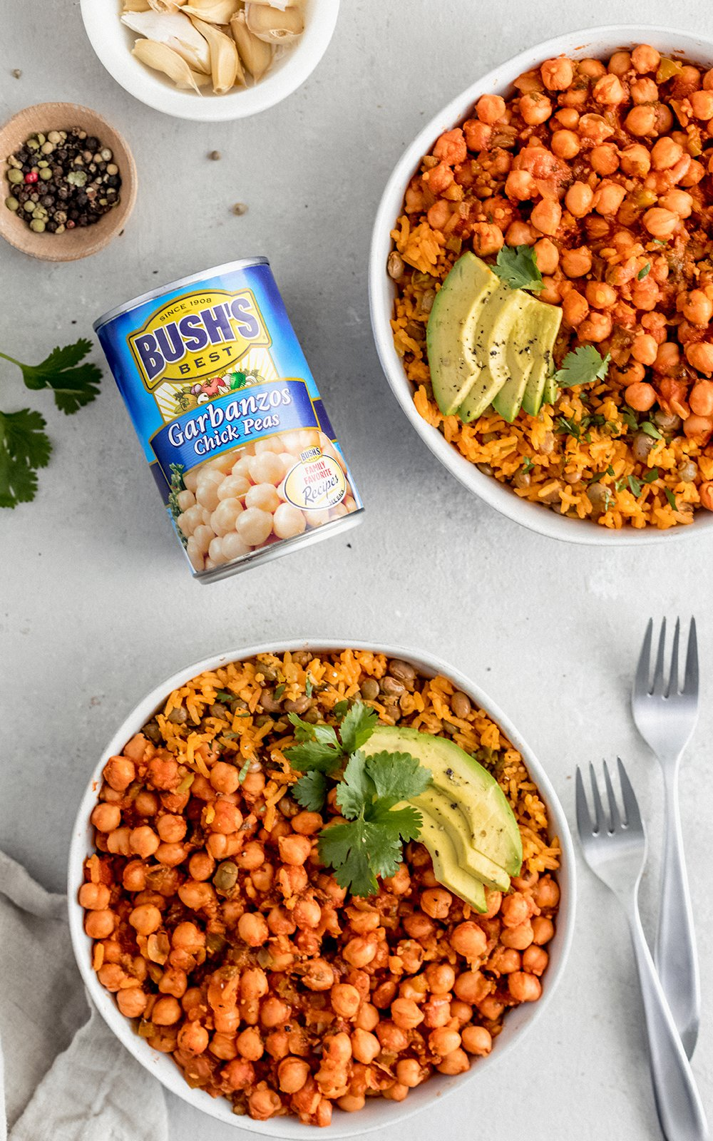 chickpeas in sofrito in two bowls next to a can of chickpeas and two forks