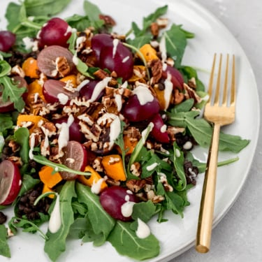 butternut squash black lentil salad with grapes on a plate with a gold fork