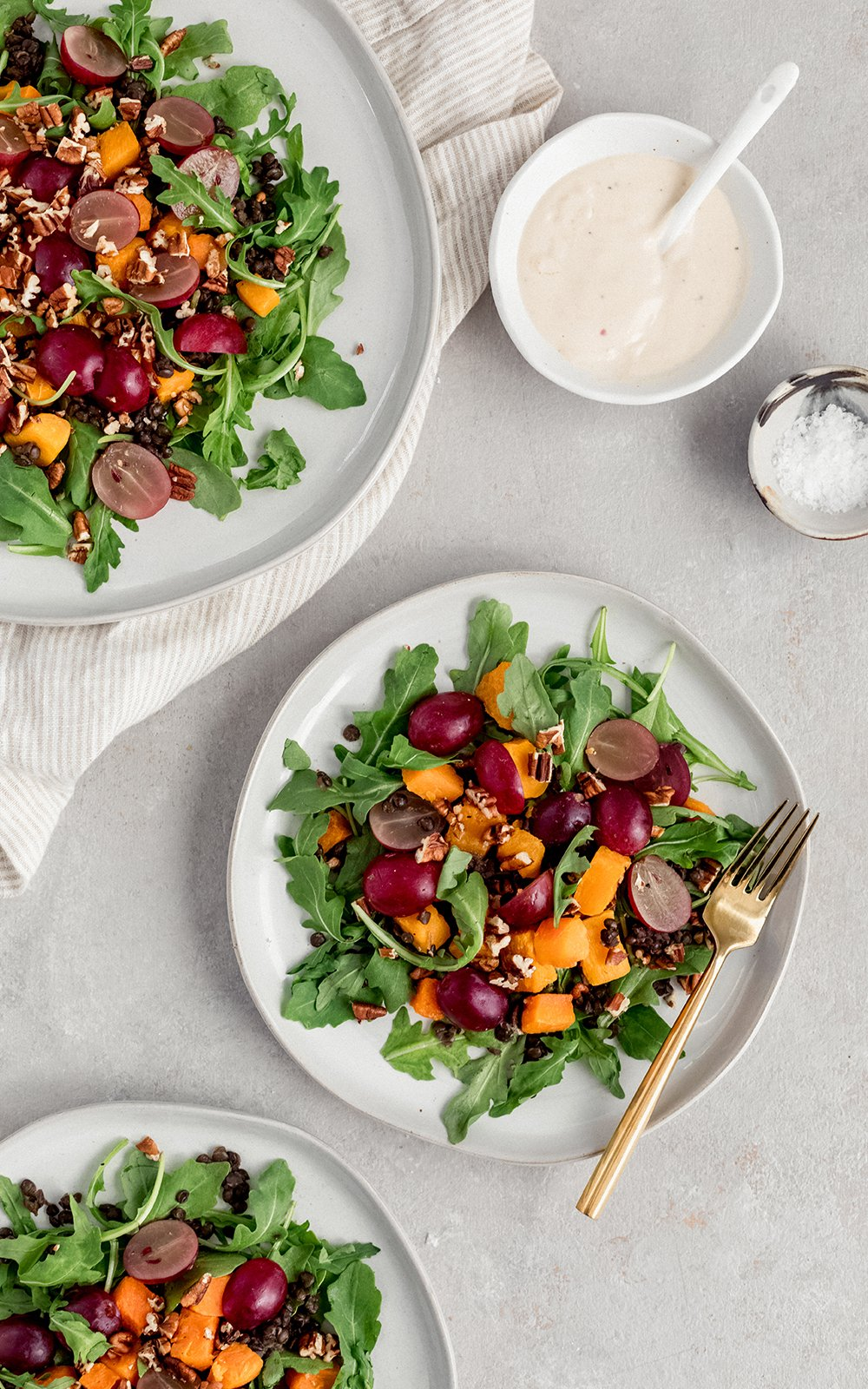 Winter roasted butternut squash black lentil salad with juicy grapes served over a bed of arugula and drizzled with a creamy tahini dressing! Full of texture, comforting and so delicious!