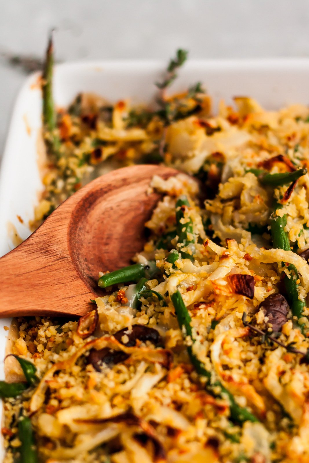 healthy green bean casserole in a baking dish with a wooden spoon