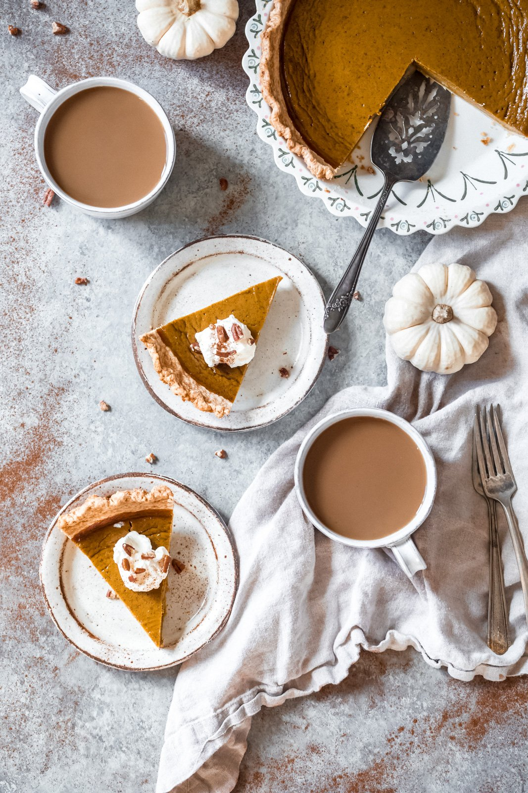 healthy pumpkin pie on two plate and in a pie pan next to two mugs of coffee and two white mini pumpkins