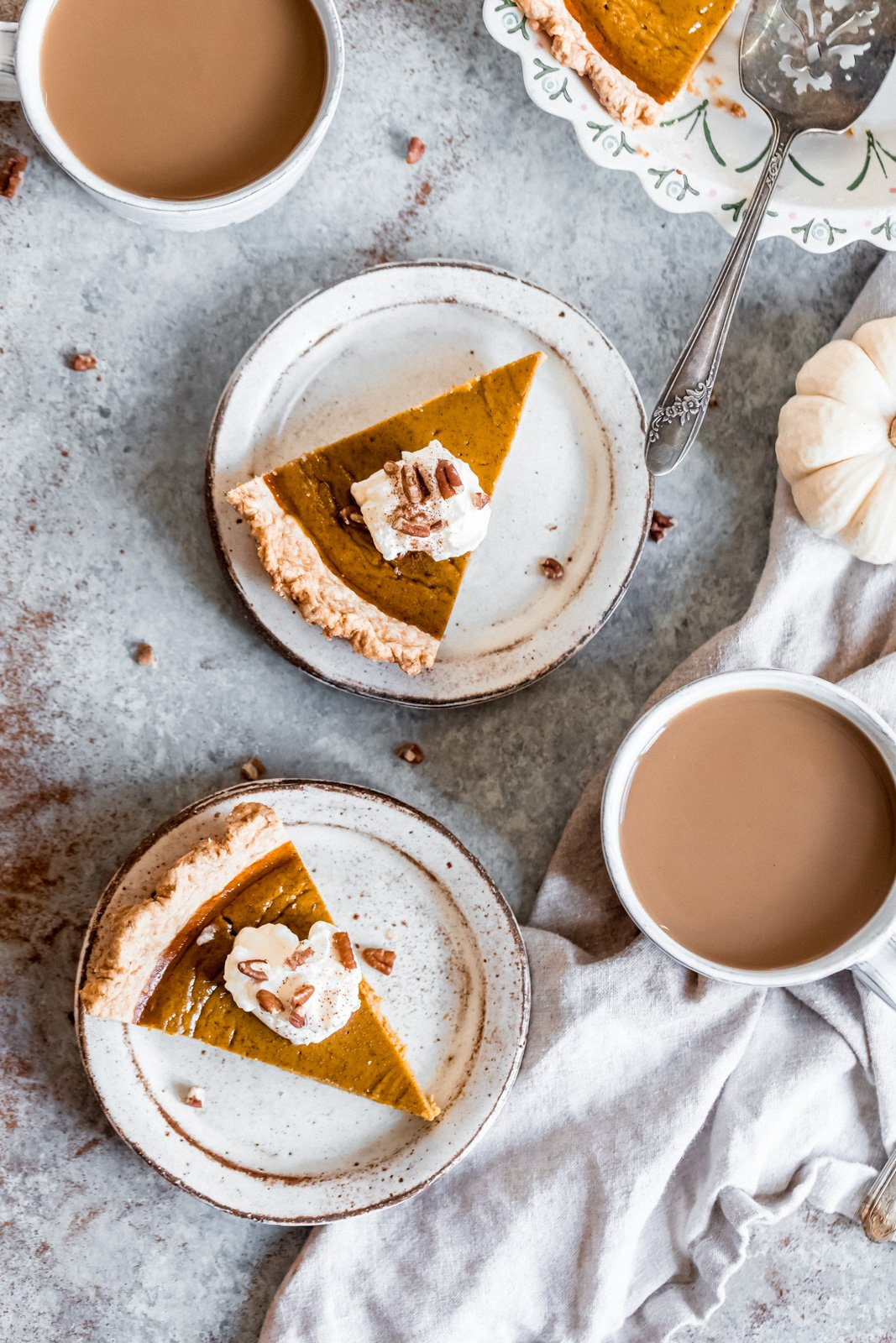 healthy pumpkin pie on two plates next to two mugs of coffee