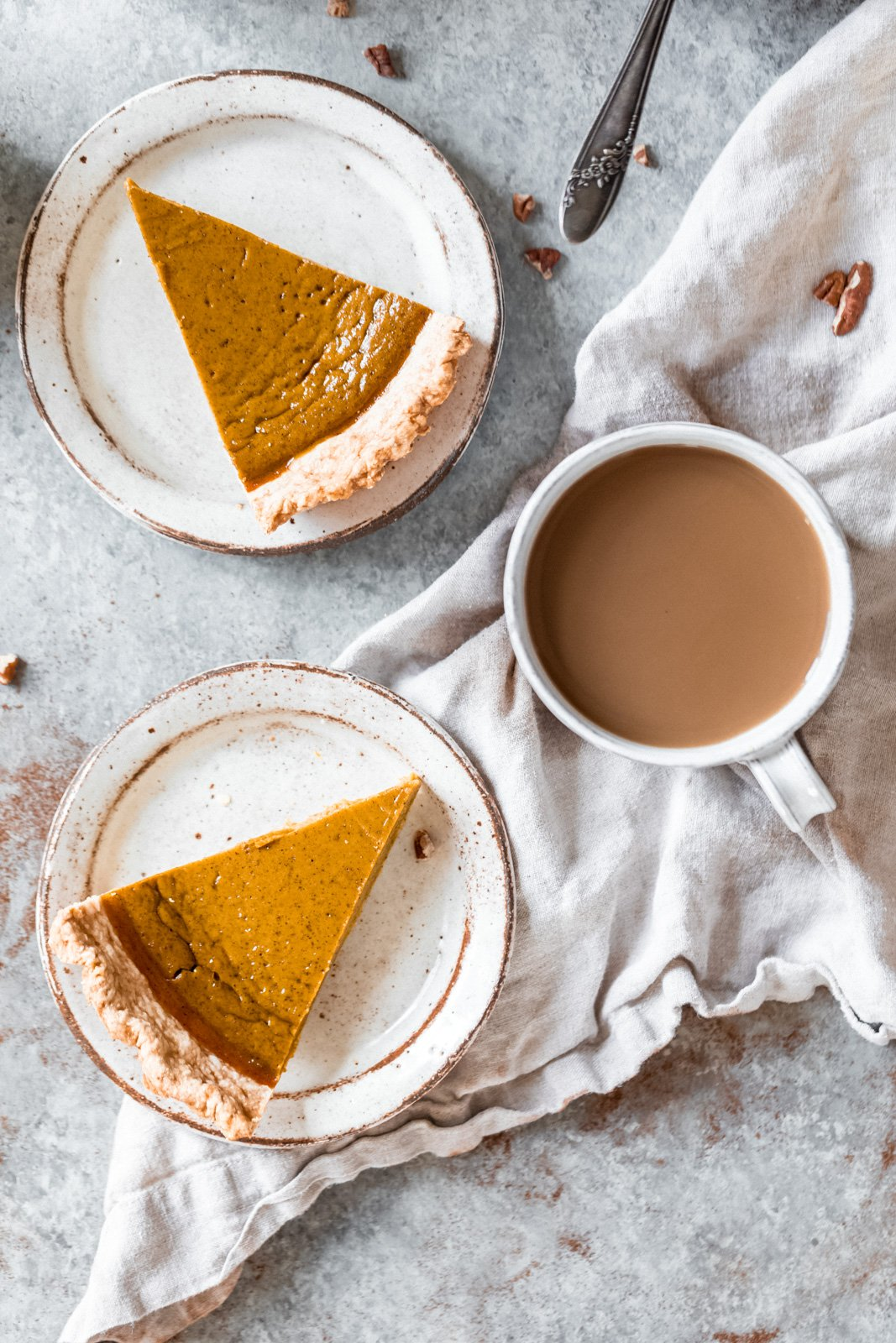 healthy pumpkin pie on two plates next to a mug of coffee