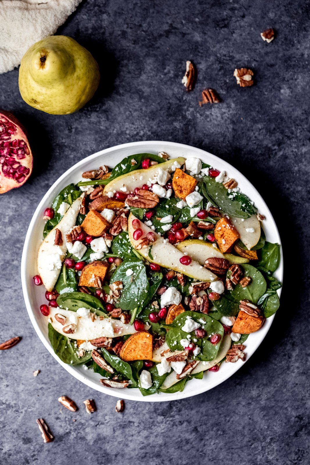 pomegranate spinach salad with pears and sweet potato in a bowl next to a pear and half of a pomegranate
