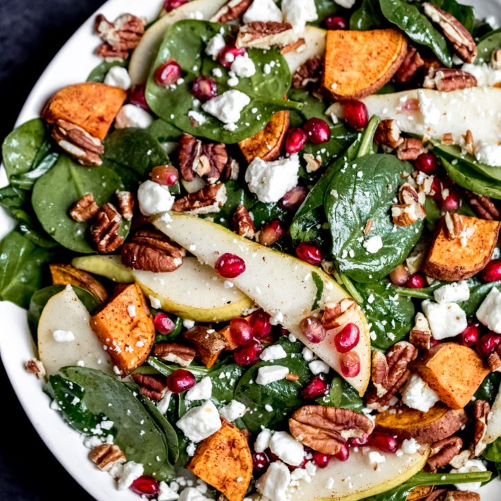 Beautiful and festive roasted sweet potato, pear and pomegranate spinach salad with creamy goat cheese, toasted pecans and a tangy balsamic dressing! Perfect for the holidays.