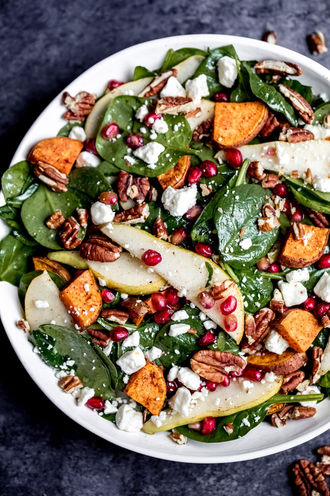 pomegranate spinach salad with pears and sweet potato in a bowl