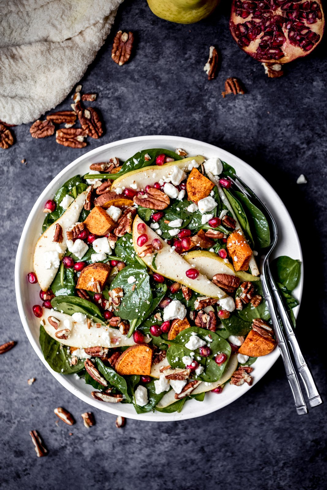 pomegranate spinach salad with pears and sweet potatoes in a bowl with two spoons