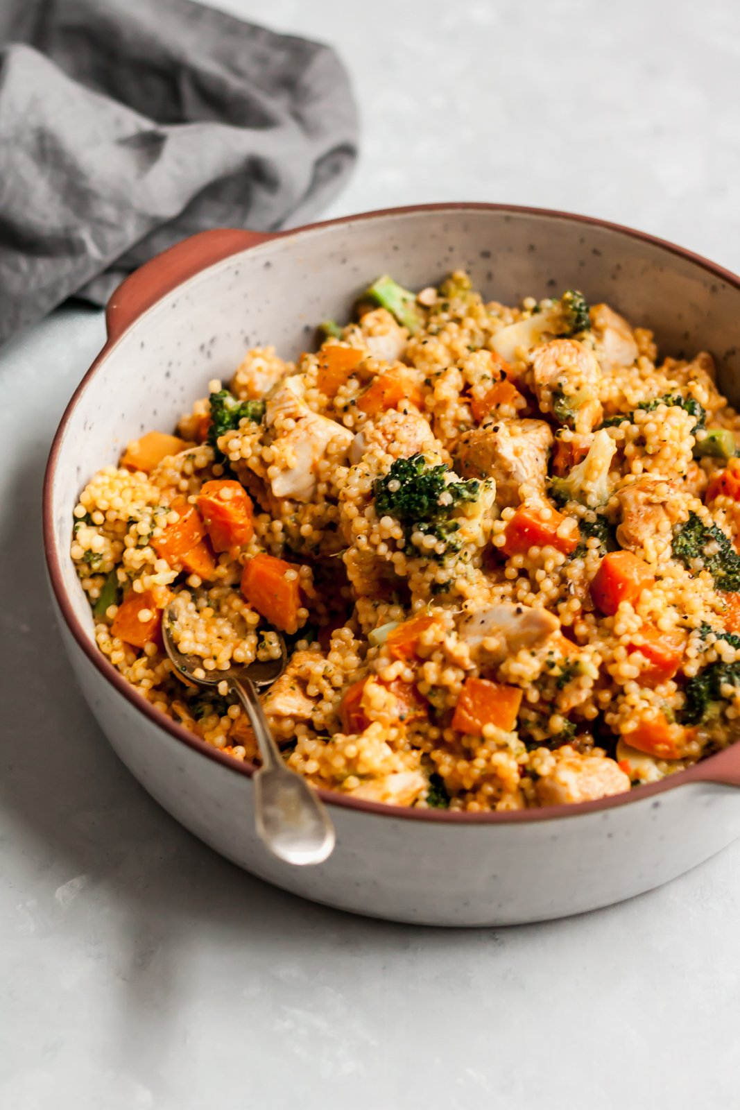 broccoli cheddar chicken couscous in a ceramic bowl with a spoon
