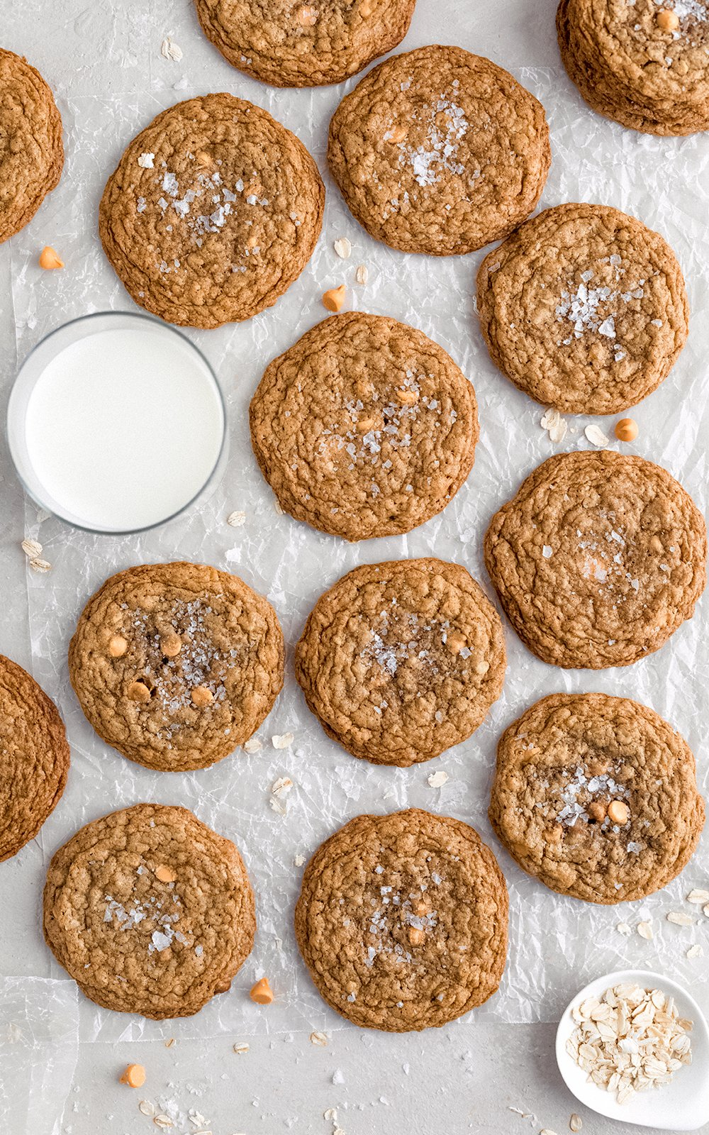 butterscotch oatmeal cookies on parchment paper next to a glass of milk