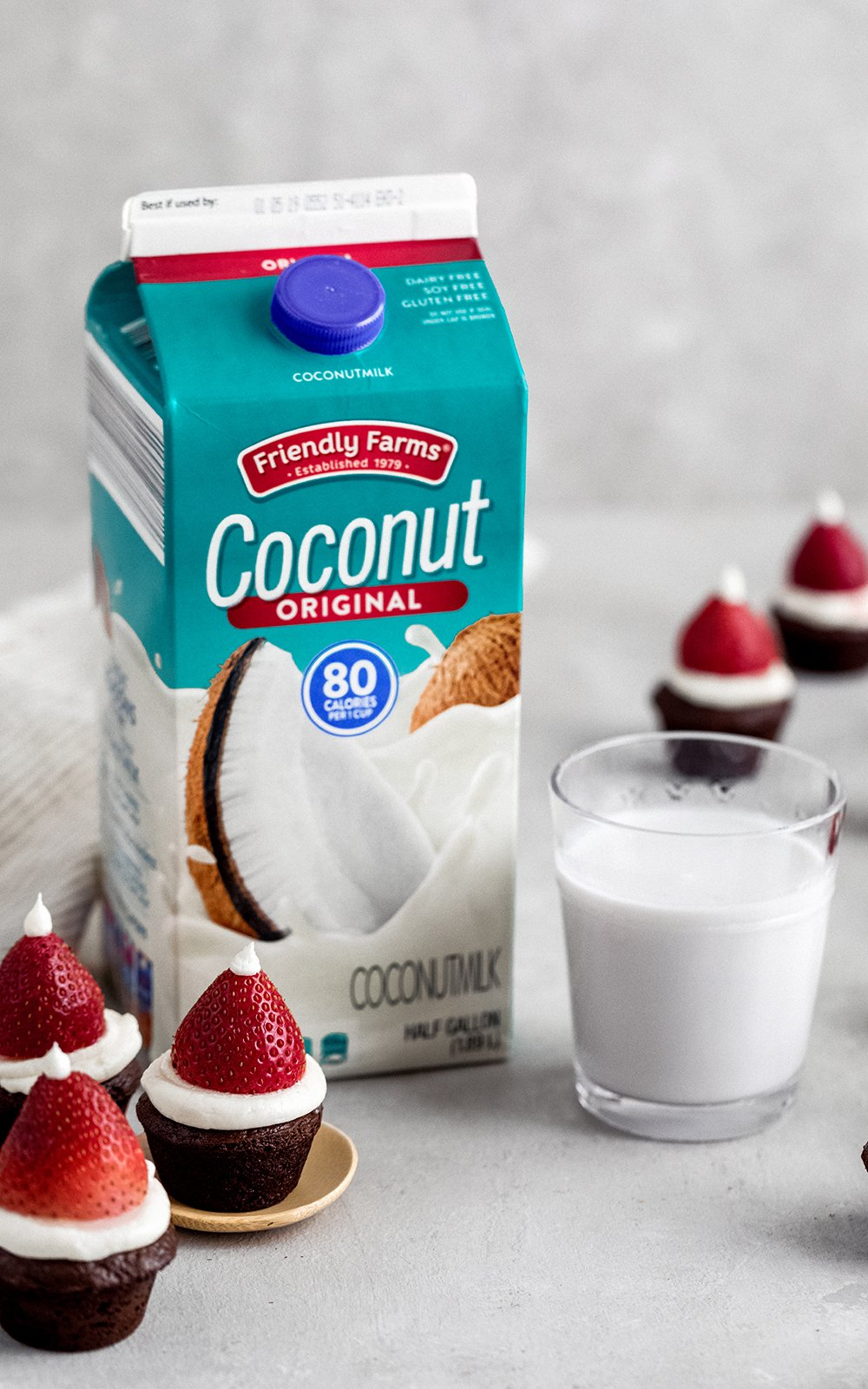 santa hat brownies next to a carton of coconut milk and a glass of coconut milk