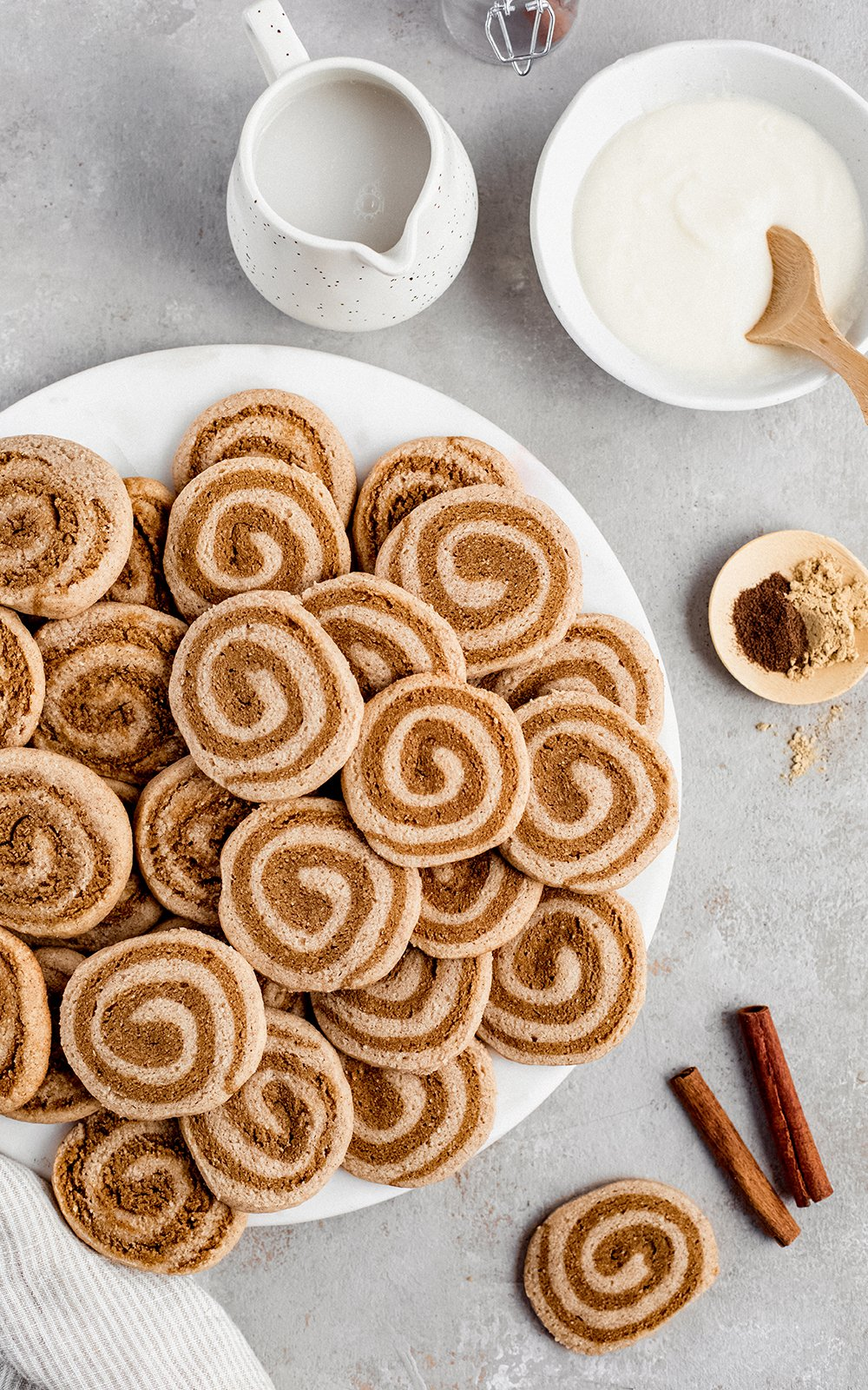 grain free gingerdoodle cookies on a plate next to a bowl of icing and cinnamon sticks