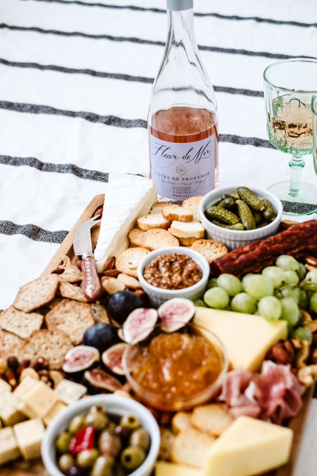 charcuterie board next to a bottle of rosé