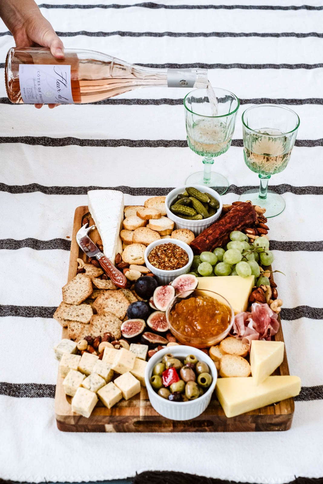 pouring rosé into two wine glasses next to a charcuterie board