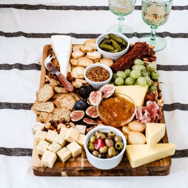 charcuterie board next to glasses of wine