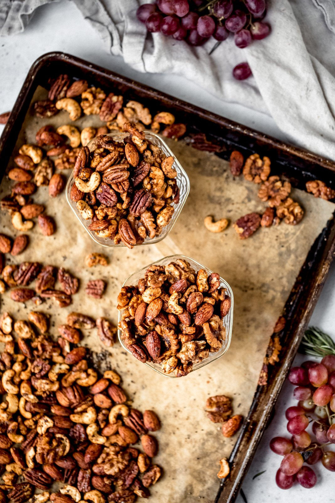 sweet and spicy nuts on a baking tray and in two glass bowls