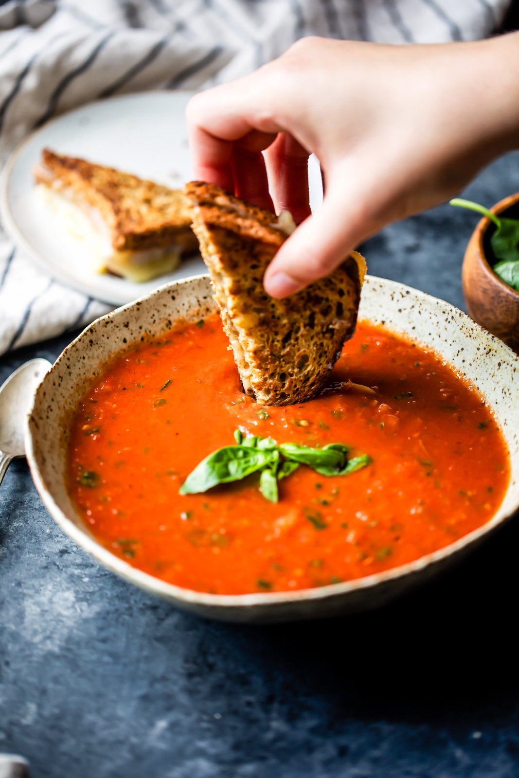 dipping a grilled cheese into homemade roasted tomato basil soup