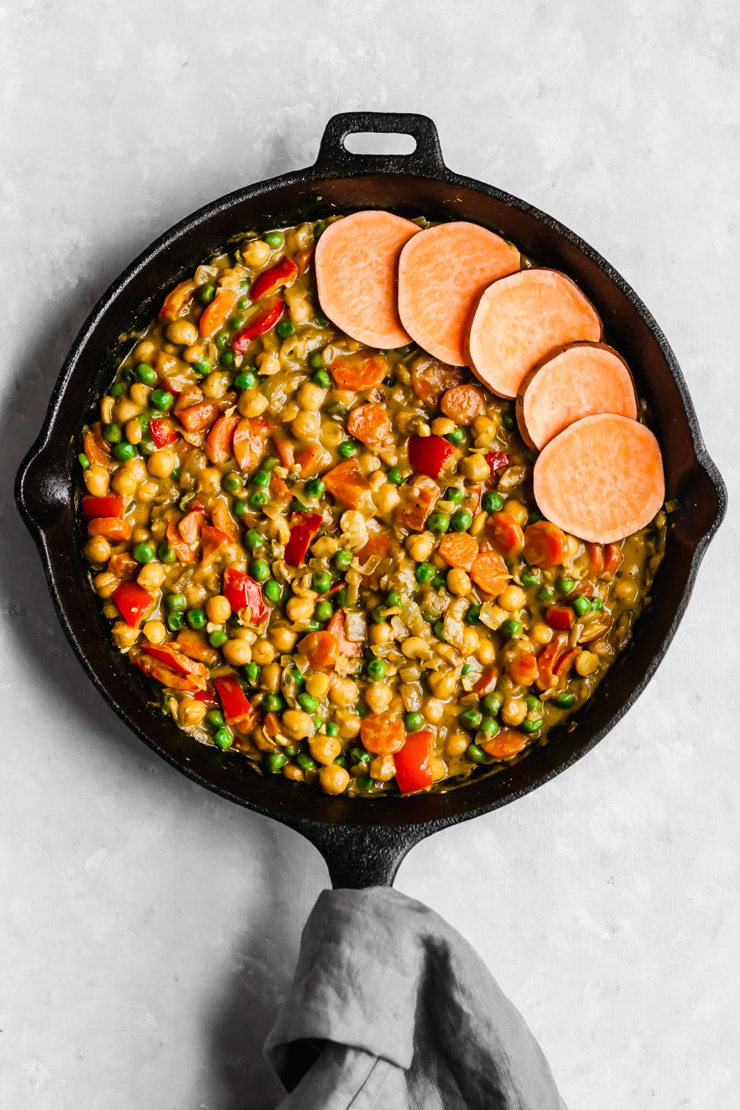 chickpea pot pie in a skillet with sweet potato rounds on top