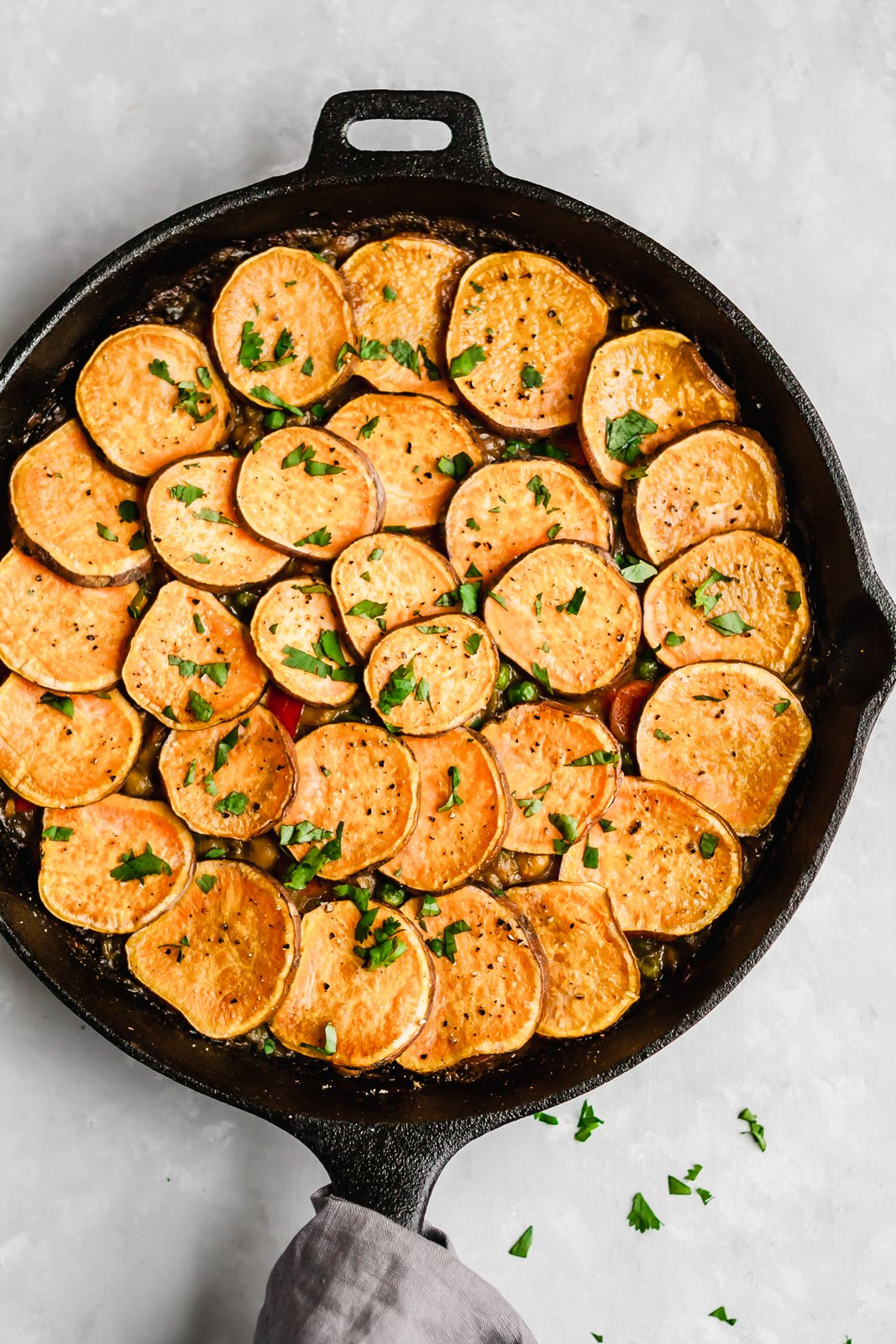 Delicious vegan and gluten-free curry chickpea pot pie recipe with a crust made of sliced sweet potatoes! This easy to make dinner is made in one pan and is packed with plant-based protein.