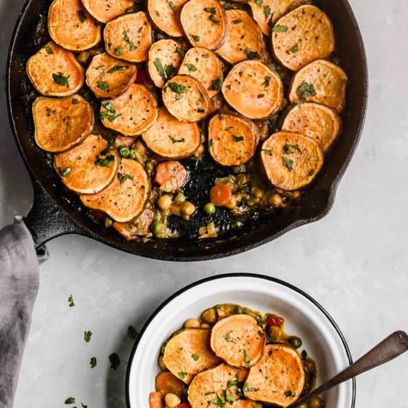 chickpea pot pie in a skillet with a bowl on the side