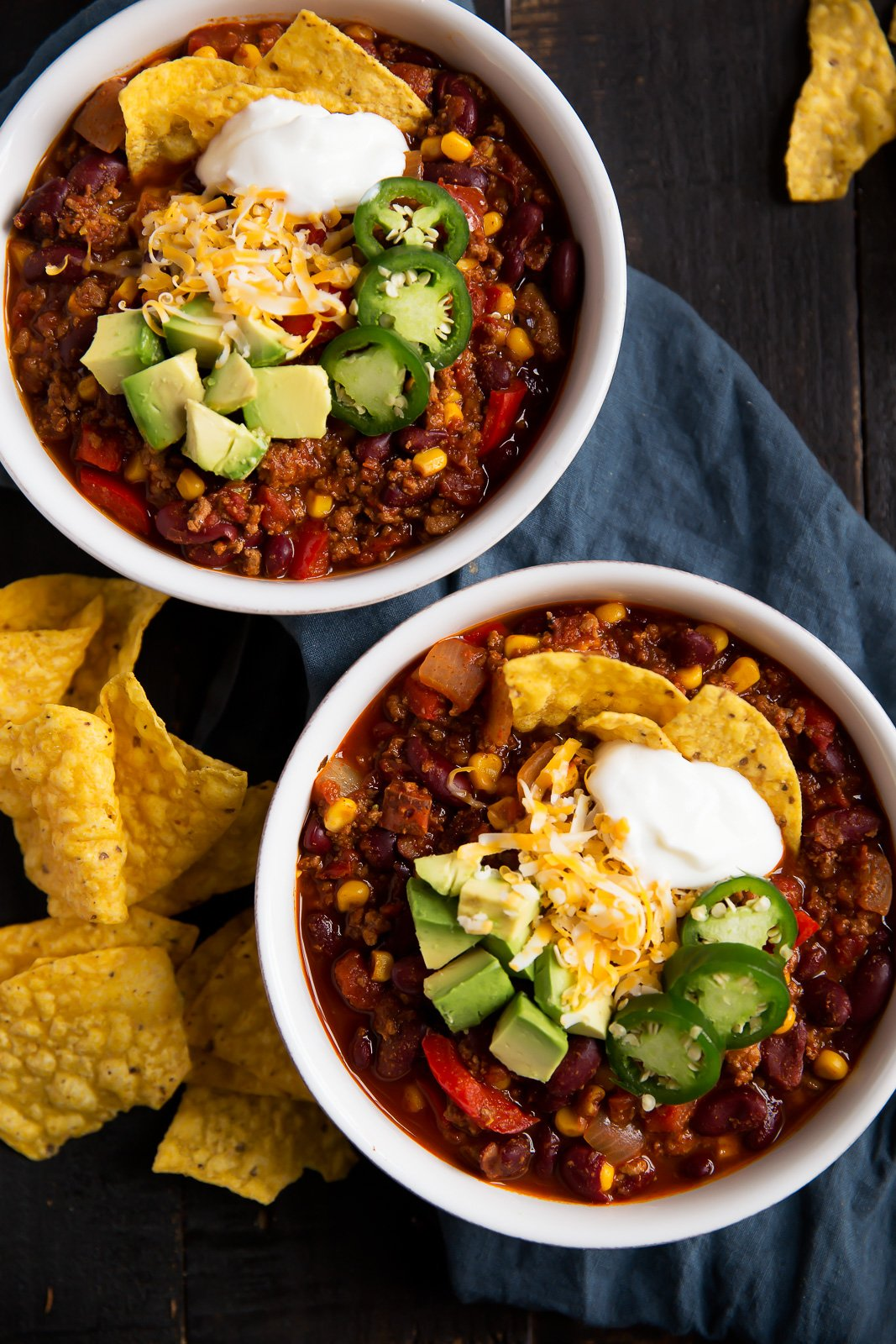 the best healthy turkey chili in two bowls topped with tortilla chips, cheese, avocado and jalapeño slices