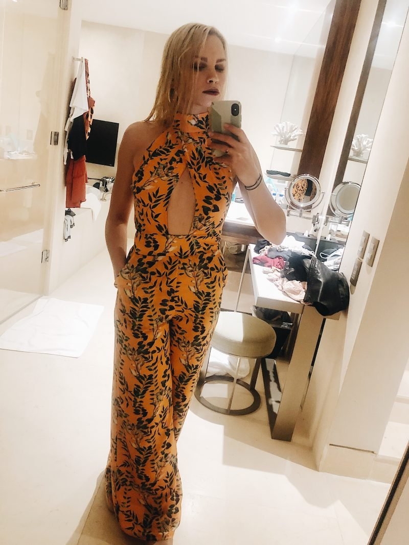 woman posing in the mirror with a yellow floral jumpsuit