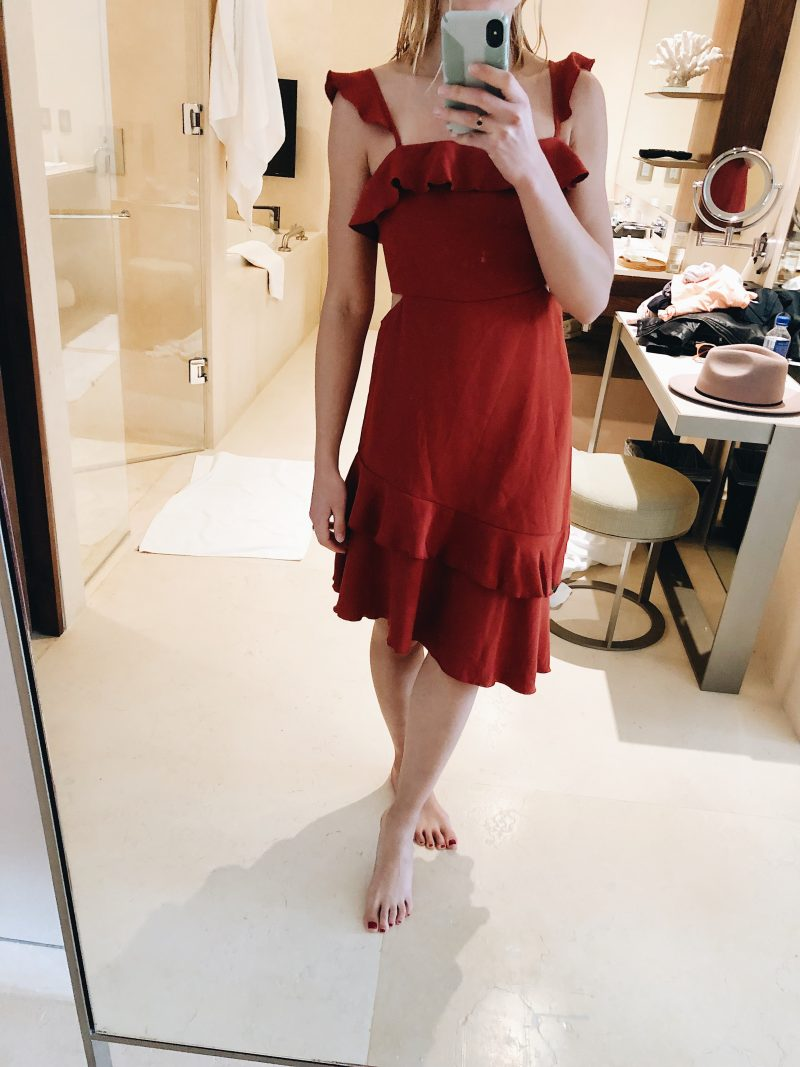 woman posing in a mirror with a red dress