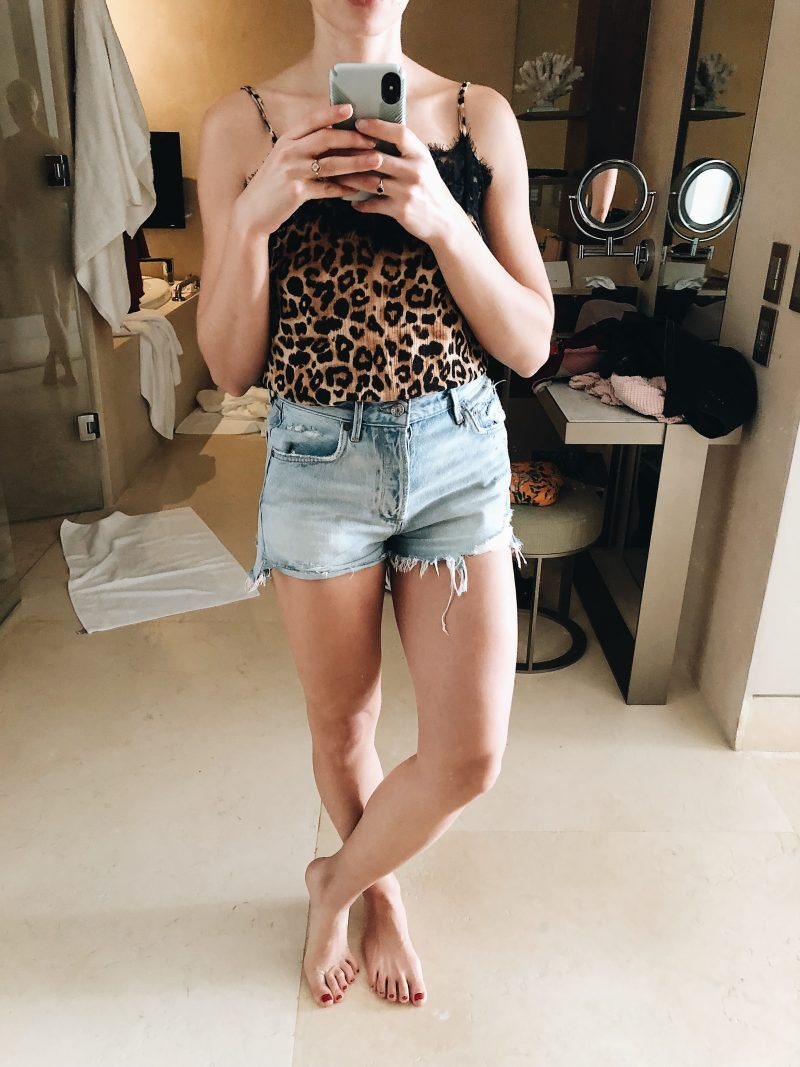 woman posing in the mirror with jean shorts and a leopard tank top