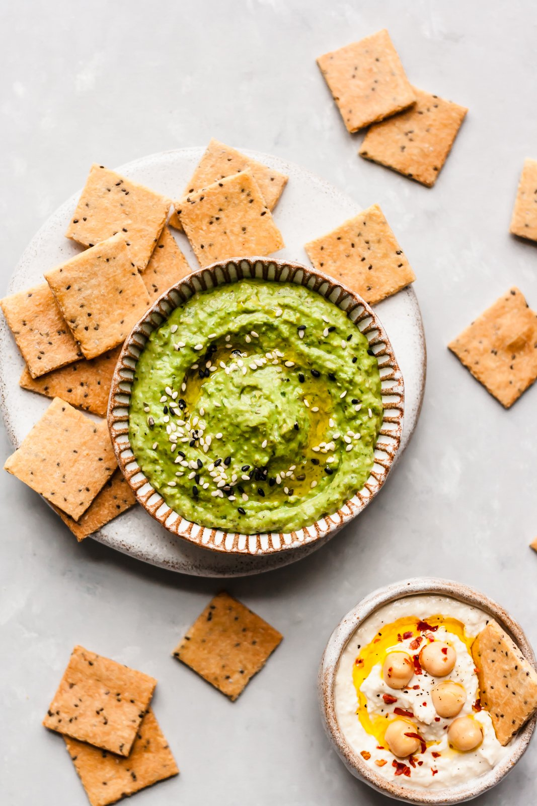 paleo crackers next to two bowls of hummus