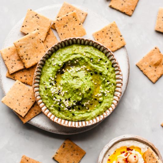 paleo crackers on a plate next to a bowl of guacamole