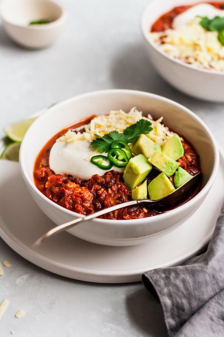 pumpkin turkey chili in a bowl with sour cream, cheese, avocado