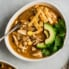 healthy white chicken chili in a bowl topped with tortilla strips and avocado slices