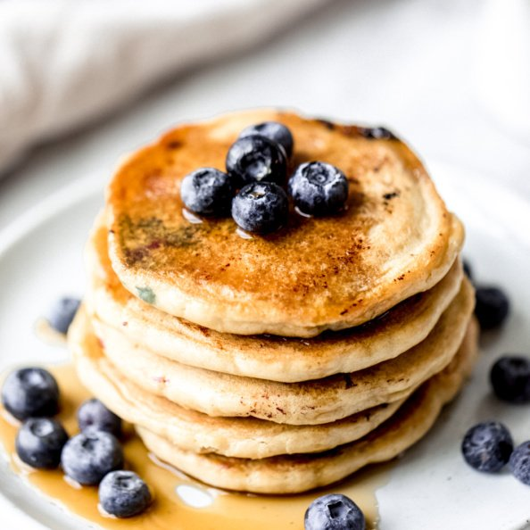 stack of pancakes on a plate topped with blueberries and maple syrup