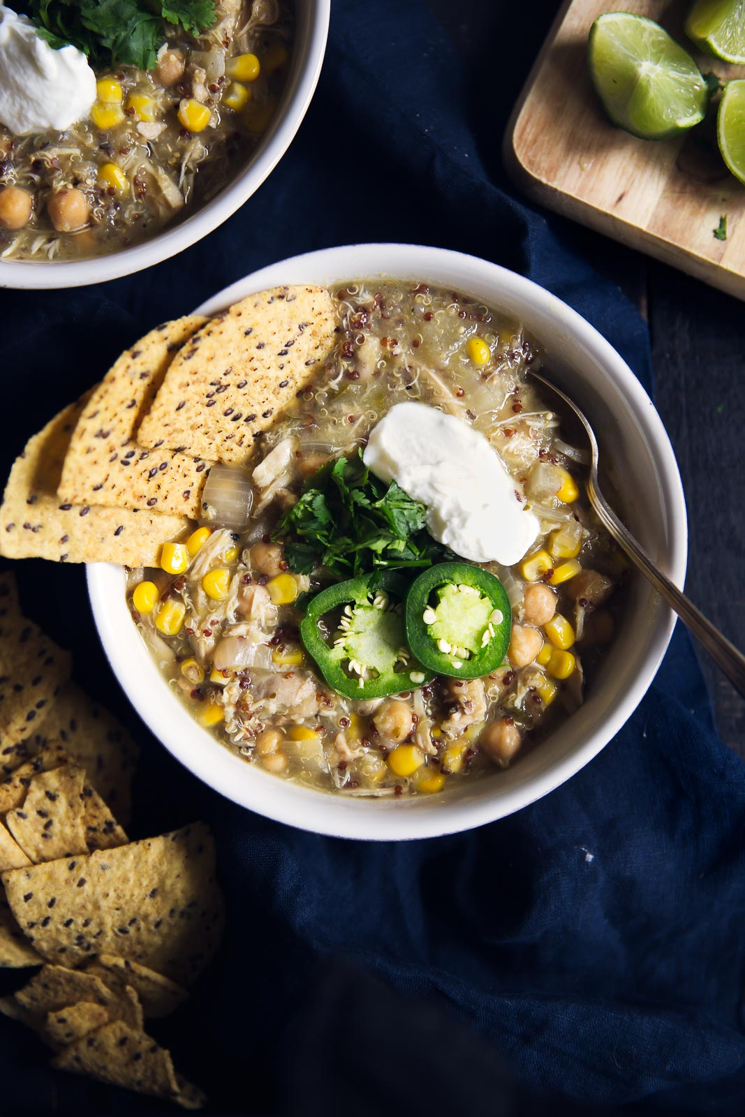 white chicken chili in a bowl with tortilla chips, jalapeño slices and sour cream