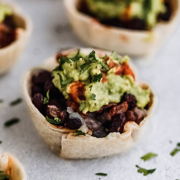 Incredible Vegetarian Black Bean Taco Cups with black beans in a chili sauce, plantains, onions, jalapeño and melted manchego on top. Topped with a simple guacamole for the ultimate crowd-pleasing appetizer. This recipe is in partnership withBUSH'S®.