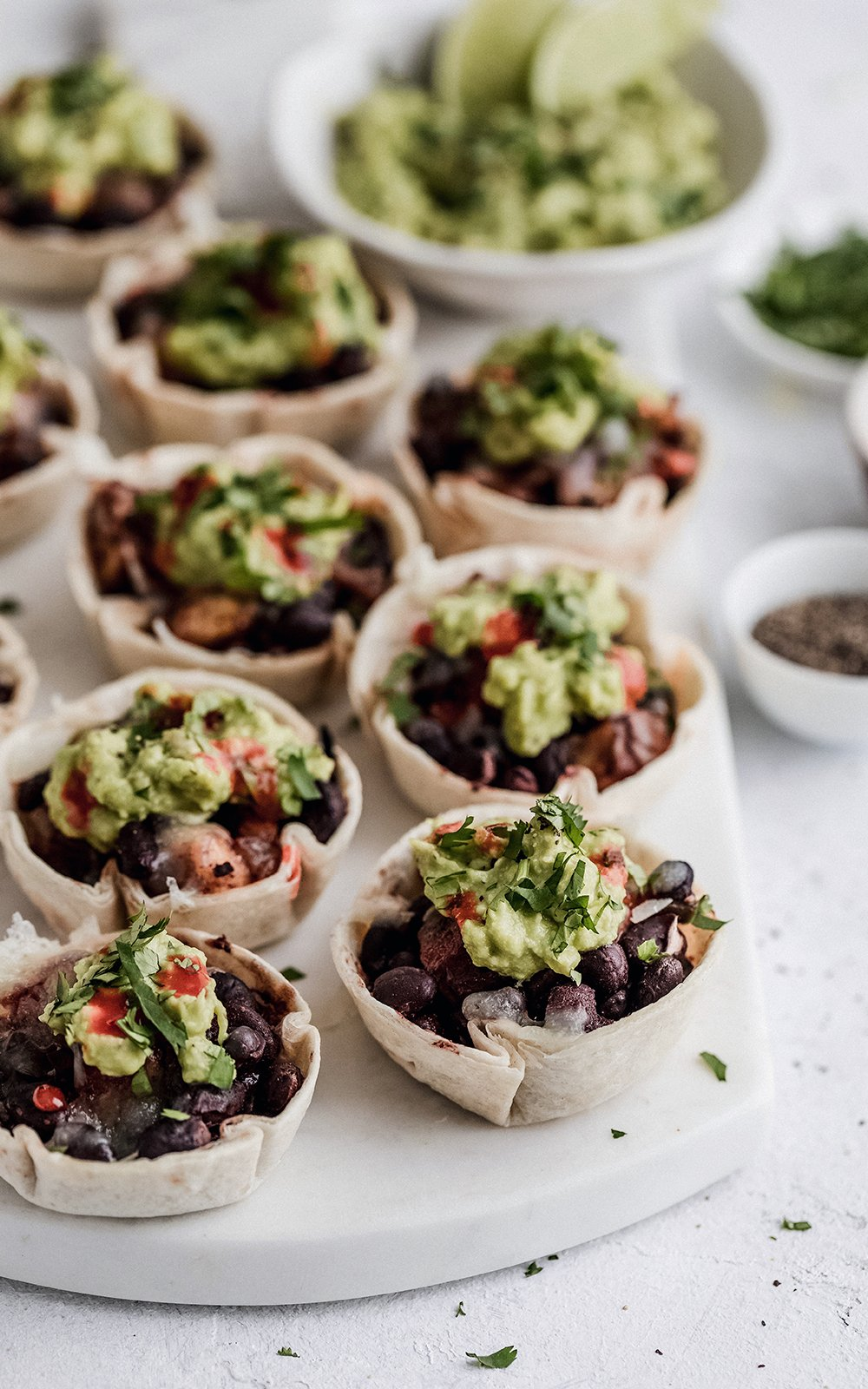black bean taco cups topped with guacamole on a marble board