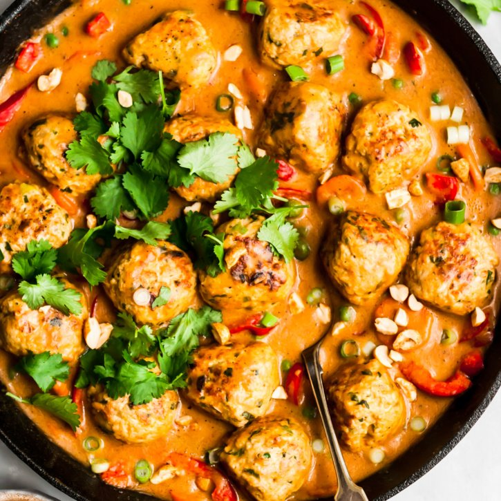 ginger chicken meatballs in a skillet pan with peanut sauce