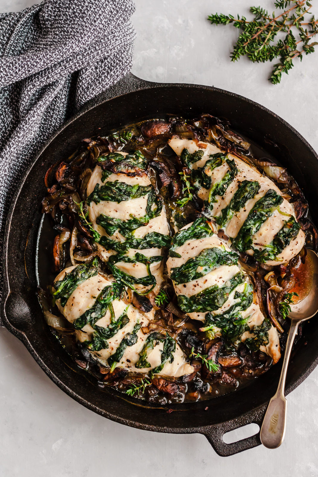 spinach goat cheese stuffed chicken breast in a skillet with a spoon on the side of the pan