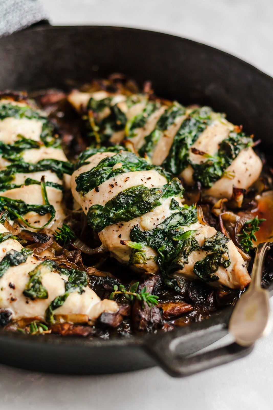 spinach and goat cheese stuffed chicken breast in a skillet