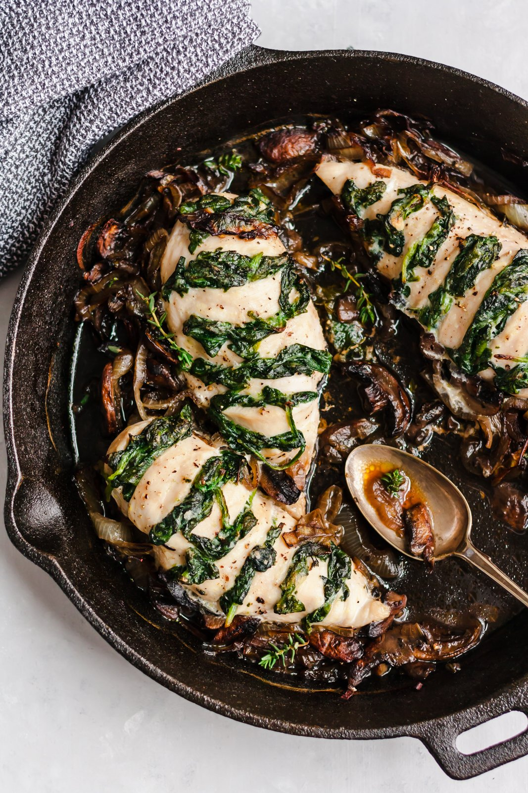 spinach stuffed chicken breasts with onions and mushrooms in a skillet with a spoon on the side