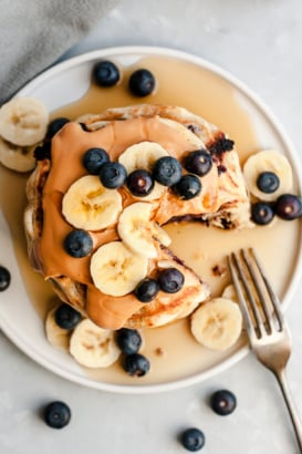 stack of vegan pancakes with blueberries, peanut butter and bananas