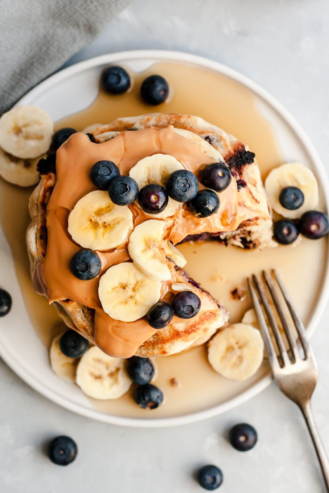 overhead shot of vegan pancakes topped with peanut butter, banana slices and blueberries