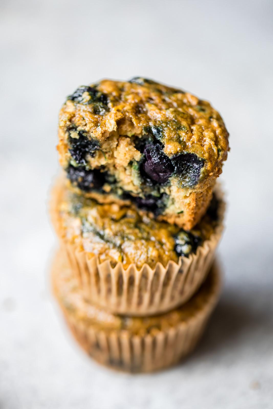 three blueberry zucchini muffins in a stack