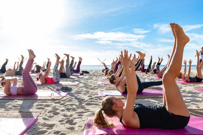 women doing yoga on a beach
