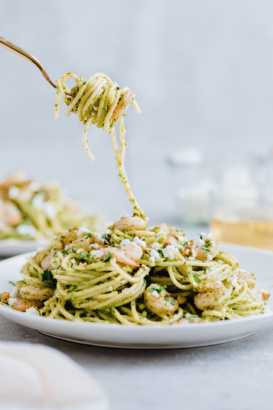 twirling shrimp pesto pasta up from a plate