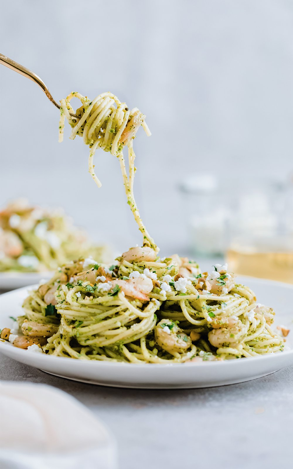 cilantro pistachio pesto shrimp pasta on a plate and twirled on a fork